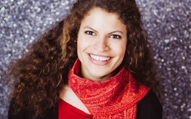 Bewerbungsfoto einer Frau mit braunen locken und rotem Schal