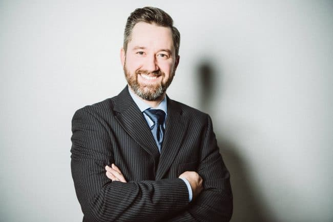 Bewerbungsfotos eines Mannes im gestreiften Anzug mit blauer Krawatte und verschränkten Armen
