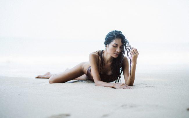 Fotografie Göttingen Asiatische Frau auf dem Bauch liegend am Strand