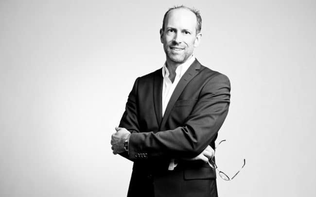 Bewerbungsfoto eines stehenden Mannes im Anzug mit Brolle in der Hand in schwarz weiß