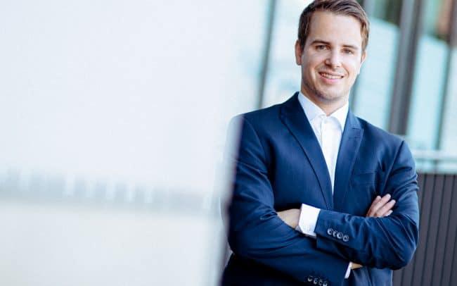 Bewerbungsfoto von einem Mann im blauen Anzug und weißem Hemd