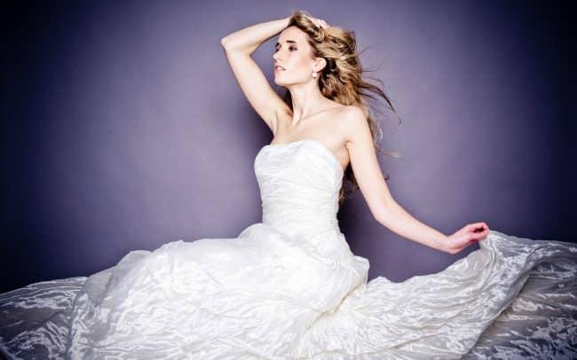 Braut sitzt vor lila Hintergrund