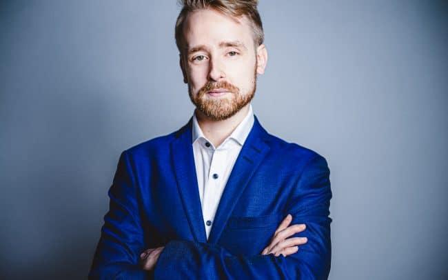 Bewerbungfoto eines Mannes im blauen Anzug mit weißem Hintergrund